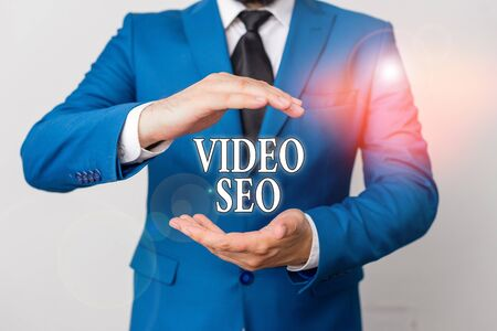 Conceptual hand writing showing Video Seo. Concept meaning the process of improving the ranking or visibility of a video Man in front of table. Mobile phone and notes on the table