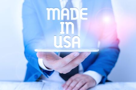 Text sign showing Made In Usa. Business photo text American brand United States Manufactured Local product Businessman in blue suite with a tie holds lap top in hands
