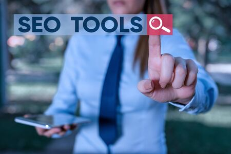 Word writing text Seo Tools. Business photo showcasing process of affecting online visibility of website or page Handsome business girl pointing with finger into empty space Stock Photo