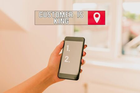 Text sign showing Customer Is King. Business photo showcasing Serve attentively and properly Deliver the needs urgently woman using smartphone office supplies technological devices inside home