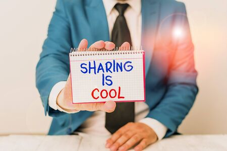 Conceptual hand writing showing Sharing Is Cool. Concept meaning giving and getting knowledge services or goods is awesome Man holds empty paper with copy space in front of him Space Stock Photo