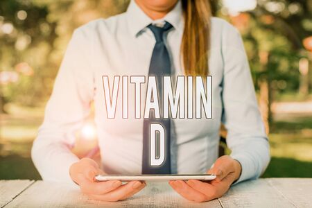 Writing note showing Vitamin D. Business concept for Nutrient responsible for increasing intestinal absorption Female business person sitting by table and holding mobile phone Фото со стока