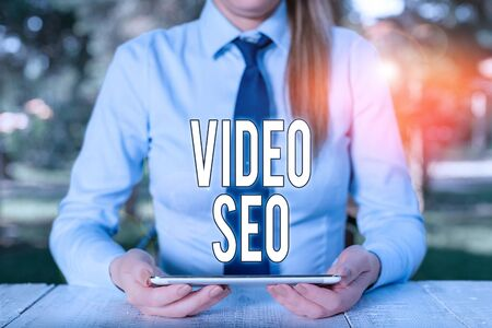 Writing note showing Video Seo. Business concept for the process of improving the ranking or visibility of a video Female business person sitting by table and holding mobile phone