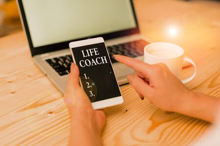 Conceptual hand writing showing Life Coach. Concept meaning someone who helps identify your goals and plan to achieve them woman with laptop smartphone and office supplies technology