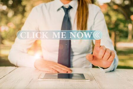 Handwriting text Click Me Now. Conceptual photo Internet helping desk Press the button Online Icon Nertwork Female business person sitting by table and holding mobile phone