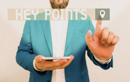 Handwriting text writing Key Points. Conceptual photo most important piece of information that is said or written Businessman in the blue suite with lap top pointing with finger
