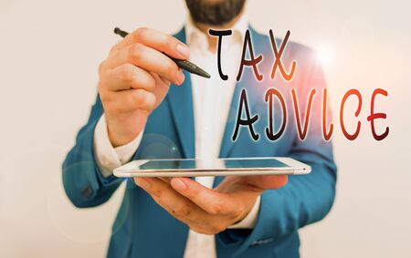 Handwriting text Tax Advice. Conceptual photo tax agent service with advanced training and knowledge of tax law Businessman pointing with pen in empty copy space Фото со стока
