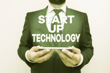 Text sign showing Start Up Technology. Business photo text Young Technical Company initially Funded or Financed Male human wear formal work suit hold smart hi tech smartphone use hands 스톡 콘텐츠
