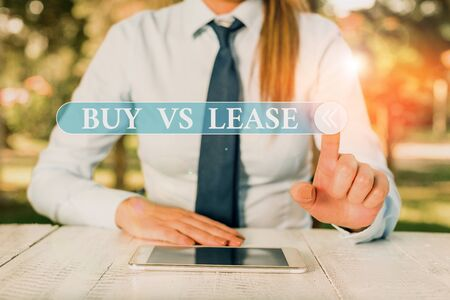 Handwriting text Buy Vs Lease. Conceptual photo Own something versus borrow it Advantages Disadvantages Female business person sitting by table and holding mobile phone