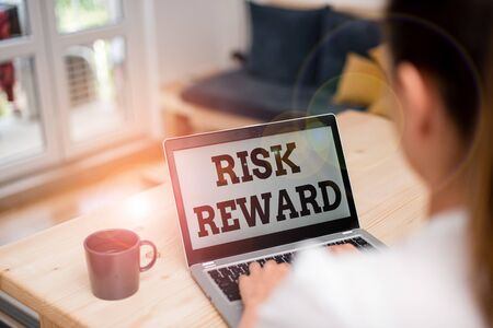 Writing note showing Risk Reward. Business concept for assess the profit potential of a trade relative to its loss woman laptop computer office supplies technological devices inside home Фото со стока