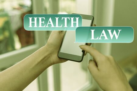 Text sign showing Health Law. Business photo text law to provide legal guidelines for the provision of healthcare woman using smartphone office supplies technological devices inside home Reklamní fotografie
