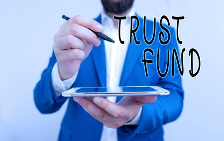Handwriting text Trust Fund. Conceptual photo money that is being held by the trustees for the beneficiaries Businessman pointing with pen in empty copy space