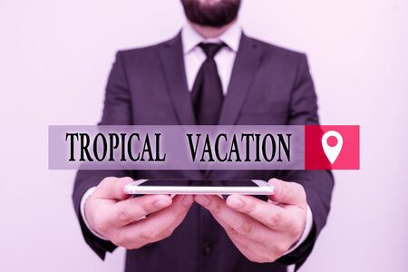 Conceptual hand writing showing Tropical Vacation. Concept meaning taking a holiday in countries either side of the equator Male human wear formal work suit hold smartphone using hand