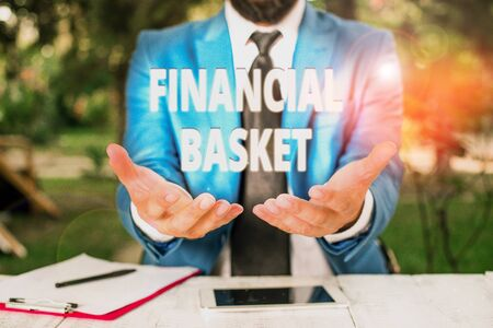 Text sign showing Financial Basket. Business photo showcasing group of securities created for simultaneous buy or sell Man with opened hands in fron of the table. Mobile phone and notes on the table Фото со стока