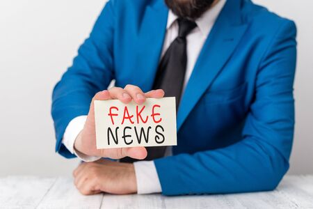 Word writing text Fake News. Business photo showcasing Giving information to showing that is not true by the media Man holds empty paper with copy space in front of him Space Stock Photo