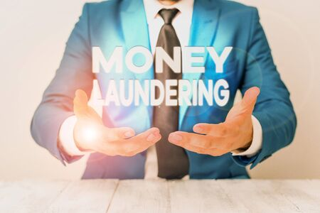 Conceptual hand writing showing Money Laundering. Concept meaning concealment of the origins of illegally obtained money Man holds empty paper with copy space in front of him Space