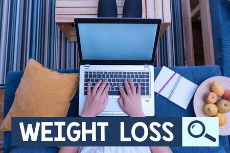 Text sign showing Weight Loss. Business photo showcasing the fact of a demonstrating or animals body weight becoming less woman laptop computer office supplies technological devices inside home Standard-Bild - 134497351