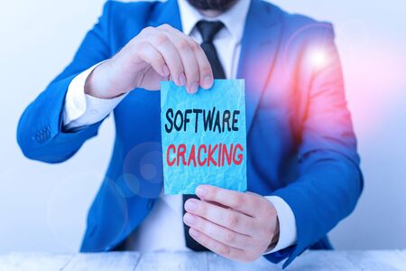 Conceptual hand writing showing Software Cracking. Concept meaning modification of software to remove or disable features Man holds empty paper with copy space in front of him Space