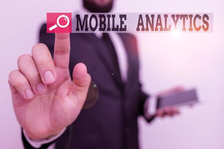 Writing note showing Mobile Analytics. Business concept for studies the behavior of mobile website visitors and users Male human wear formal work suit hold hi tech smartphone use hand