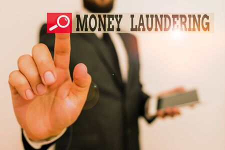 Writing note showing Money Laundering. Business concept for concealment of the origins of illegally obtained money Male human wear formal work suit hold hi tech smartphone use hand