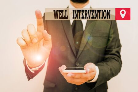 Writing note showing Well Intervention. Business concept for work carried out on gas well to alter or analysisage its health Male human wear formal work suit hold smartphone using hand 版權商用圖片