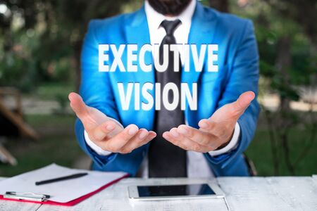 Text sign showing Executive Vision. Business photo showcasing inspires those around them to move toward Creates solution Man with opened hands in fron of the table. Mobile phone and notes on the table Stock Photo