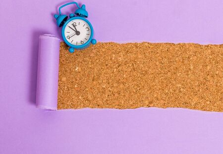 Alarm clock and torn cardboard placed above a wooden classic table backdrop
