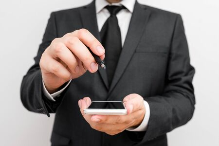 Male human wear formal work suit hold smart hi tech smartphone use one hand