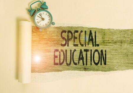 Text sign showing Special Education. Business photo showcasing form of learning given to students with mental challenges Alarm clock and torn cardboard placed above a wooden classic table backdrop