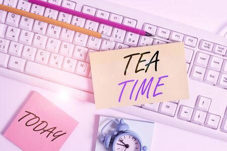 Text sign showing Tea Time. Business photo showcasing the time in the afternoon when some showing eat a small meal Flat lay above empty note paper on the pc keyboard pencils and clock