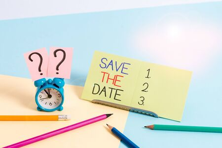 Text sign showing Save The Date. Business photo text Systematized events Scheduled activity Recorded Filed Mini size alarm clock beside stationary placed tilted on pastel backdrop Stockfoto - 134623028