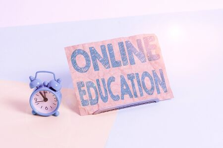 Text sign showing Online Education. Business photo text kind of learning that takes place via the Internet Mini size alarm clock beside a Paper sheet placed tilted on pastel backdrop