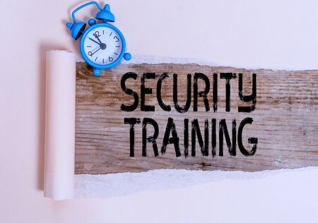 Text sign showing Security Training. Business photo showcasing providing security awareness training for end users Alarm clock and torn cardboard placed above a wooden classic table backdrop