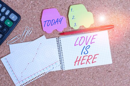 Text sign showing Love Is Here. Business photo text Roanalysistic feeling Lovely emotion Positive Expression Care Joy Desk notebook paper office cardboard paperboard study supplies table chart