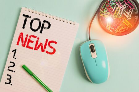 Text sign showing Top News. Business photo showcasing information that is being received and broadcast about an event Notebook and writing equipment with computer mouse above pastel backdrop Stock Photo