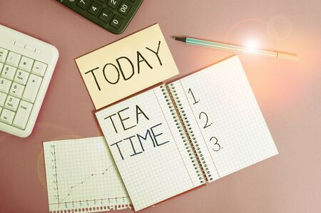 Handwriting text Tea Time. Conceptual photo the time in the afternoon when some showing eat a small meal Writing equipments and computer stuffs placed above classic wooden table 版權商用圖片