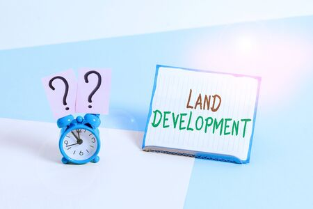 Conceptual hand writing showing Land Development. Concept meaning process of acquiring land for constructing infrastructures Alarm clock beside a Paper sheet placed on pastel backdrop