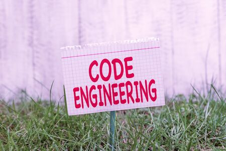 Conceptual hand writing showing Code Engineering. Concept meaning application of engineering to the development of software Mathematic paper attached to a stick and placed in the grassy land