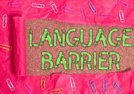 Conceptual hand writing showing Language Barrier. Concept meaning difficulties in communication Speaking different language Paper clip and torn cardboard on wood classic table backdrop