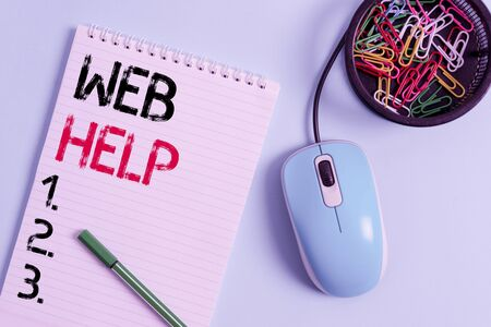 Text sign showing Web Help. Business photo showcasing procedural or reference information delivered through computer Notebook and writing equipment with computer mouse above pastel backdrop Stock Photo