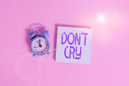 Writing note showing Don T Cry. Business concept for Shed tears typically as an expression of distress pain or sorrow Vintage alarm clock wakeup blank notepad sticky note colored background
