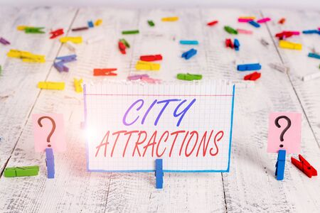 Conceptual hand writing showing City Attractions. Concept meaning place that showing visit for pleasure and interest Crumbling sheet with paper clips placed on the wooden table