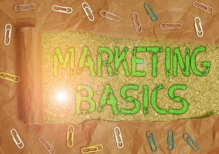 Conceptual hand writing showing Marketing Basics. Concept meaning activities a company takes to promote and sell products Paper clip and torn cardboard on wood classic table backdrop Stock Photo