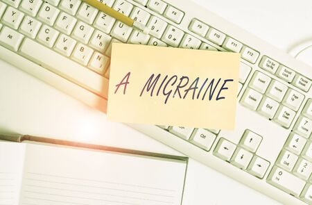 Word writing text A Migraine. Business photo showcasing recurrent throbbing headache that affects one side of the head White pc keyboard with empty note paper and paper clips above white background