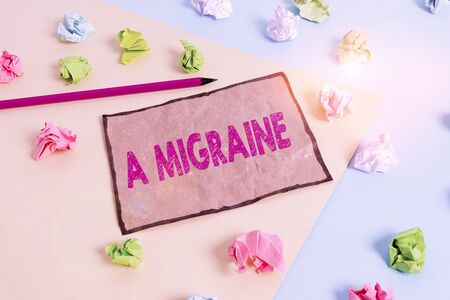 Handwriting text writing A Migraine. Conceptual photo recurrent throbbing headache that affects one side of the head Colored crumpled papers empty reminder blue yellow background clothespin Reklamní fotografie
