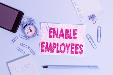 Text sign showing Enable Employees. Business photo showcasing giving employees with the information they need to succeed Alarm clock clips notepad smartphone rubber band marker colored background 写真素材