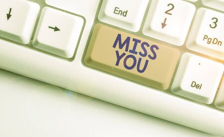 Handwriting text Miss You. Conceptual photo Feeling sad because you are not here anymore loving message White pc keyboard with empty note paper above white background key copy space