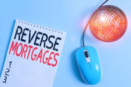 Word writing text Reverse Mortgages. Business photo showcasing borrower to access the unencumbered value of the property Blank notebook and clips with computer mouse placed above pastel backdrop