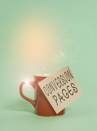 Text sign showing Conversion Pages. Business photo showcasing appears in response to clicking on a search engine Coffee tea cup mug colored sticky note lying beautiful pastel background 写真素材