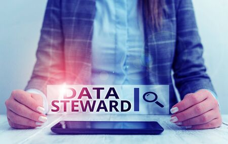 Handwriting text writing Data Steward. Conceptual photo responsible for utilizing an organization s is data governance Business woman sitting with mobile phone on the table Stock fotó
